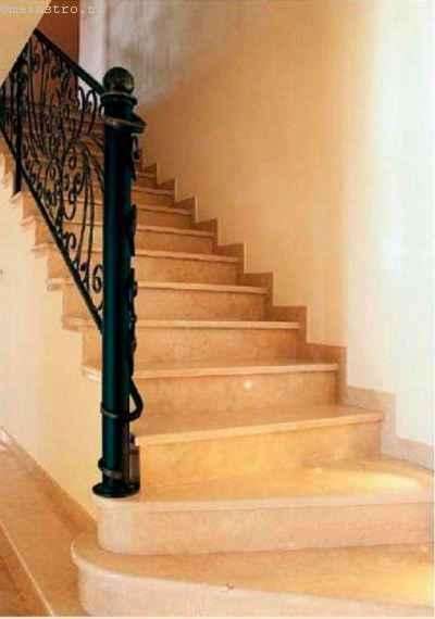 Для отделки лестницы с нижними забежными ступенями использован мрамор бежевого оттенка, гармонирующий с покрытием пола и металлической вязью балюстрады