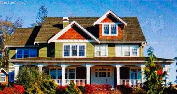 Дом серо-зелено-коричневых оттенков хорошо вписывается в ландшафт