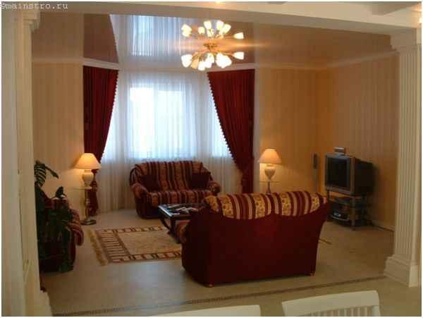 Глянцевый натяжной потолок в гостиной с люстрой