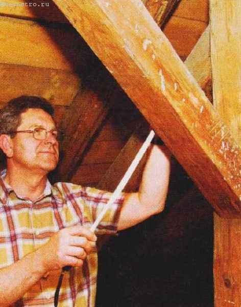На фото кровельщик осматривает балку до начала ремонта скатной крыши