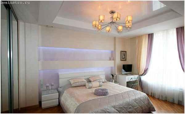 На фото натяжной потолок с подвесной люстрой в спальне