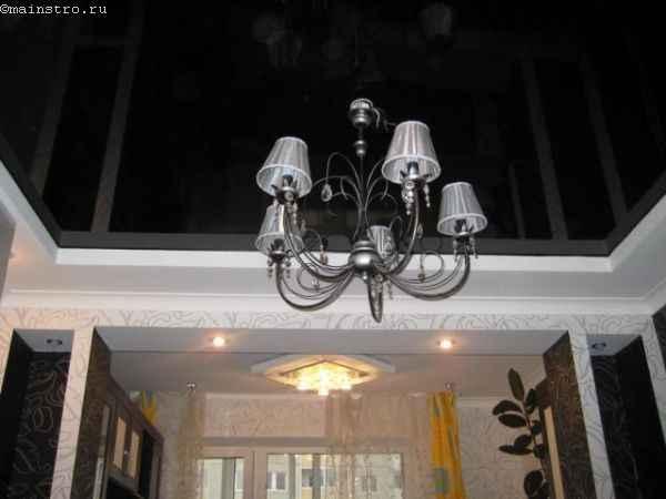 На фото чёрно-белые натяжные потолки с подвесной люстрой